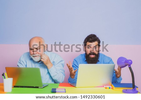 Businessman teamwork and partnership concept. Two businessmen using computer together discussing news or movie. Two people meeting and discuss in office