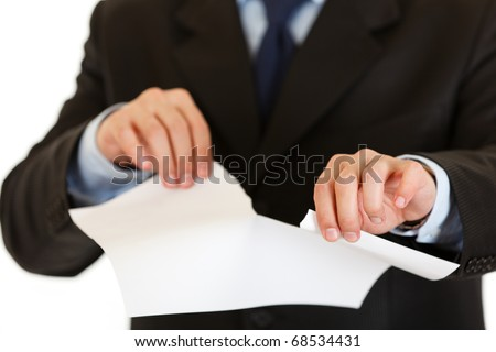 Businessman tearing sheet of white paper isolated on white. Close-up.
