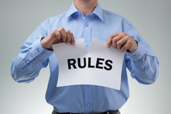 Businessman tearing up the rules or rulebook concept for innovation, creativity or mischief