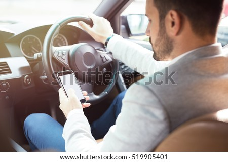 Businessman texting on his mobile phone while driving. Dangerous driver.