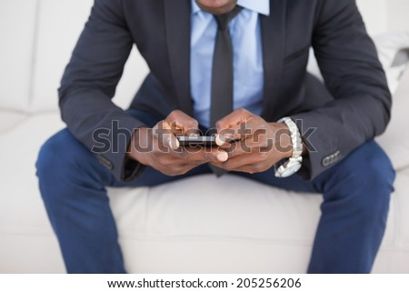 Businessman texting on phone on sofa at home in the living room