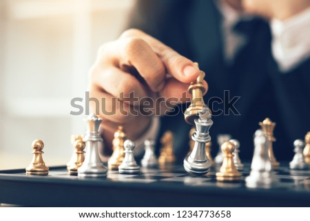 Businessman thinking about strategy concept and hand moving the king in a chess game for win. #1234773658