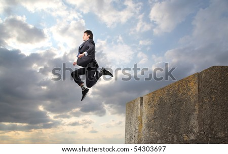 Businessman throwing himself from a rock into the void