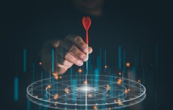 Businessman throwing red arrow dart to virtual target dart board. Setup objectives and target for business investment concept, Digital marketing, Business goal and technology concept.