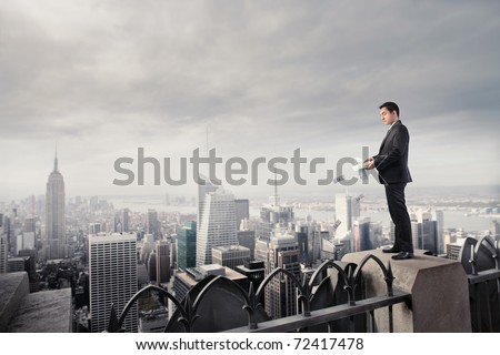 Businessman throwing some banknotes from a skyscraper