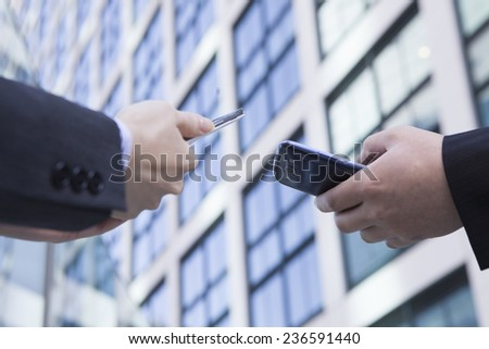 Businessman to operate the smart phone in front of the office building #236591440