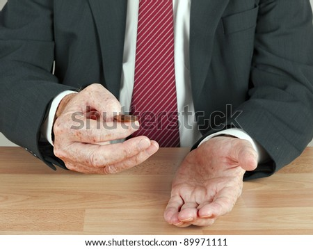 Businessman tossing UK coin at desk