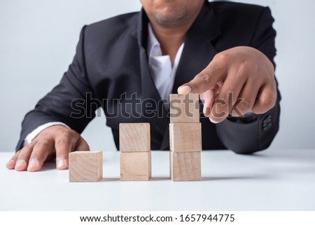 Businessman touches the woodblocks placed on the  table, concept: leadership planning strategy objective for management risk investment finance, achievement chart tower graph  for organization
