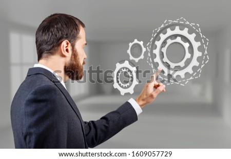 Businessman touches virtual gears cooperation. In the empty office background.