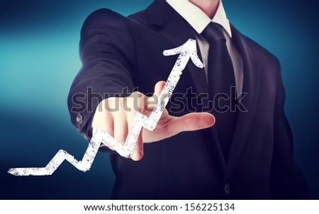 Businessman Touching a Arrow Indicating Growth on navy blue background