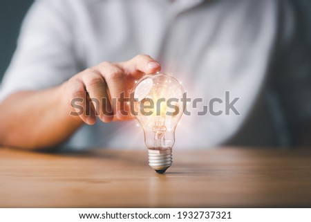 Businessman touching a bright light bulb. Concept of Ideas for presenting new ideas Great inspiration and innovation new beginning.