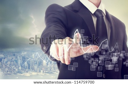 Businessman Touching a Graph above a City