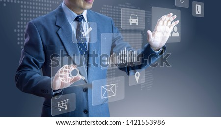 Businessman touching futuristic modern virtual touch screens of a cloud system, selecting items in an application