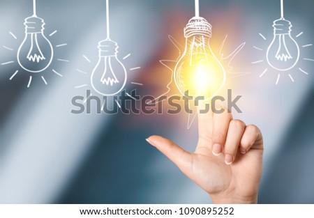 Businessman touching light bulbs #1090895252