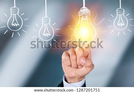 Businessman touching light bulbs #1287201751