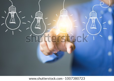 Businessman touching light bulbs, new ideas with innovative technology and creativity.