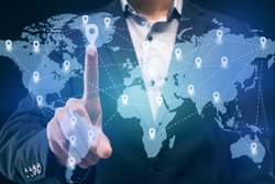 Businessman touching location on worldwide business map proected on interactive screen, worldwide business concept