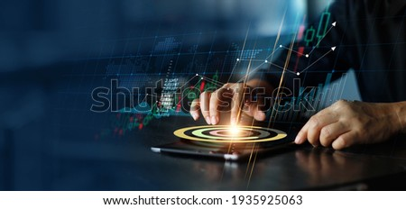 Businessman touching pie chart on tablet and analyzing sales data and economic growth graph chart. Financial. Stock market and banking on dark background.