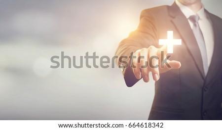 Businessman touching plus sign positive thing, such as benefits, profit, development, CSR, copy space