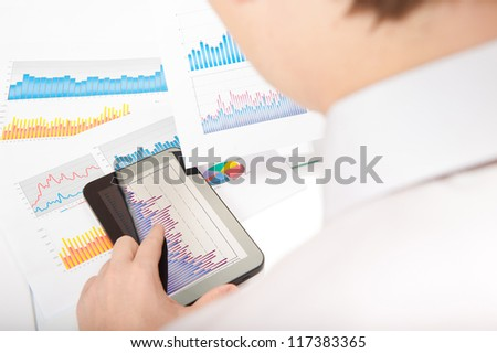 Businessman touching touchscreen digital tablet and analyzing financial chart