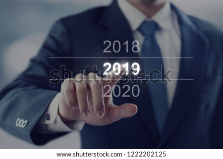 Businessman touching year 2019. Business new year card concept. #1222202125