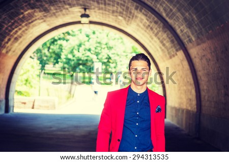 Businessman traveling in New York. Dressing in red blazer, pocket square, blue collarless shirt, a young guy walking through under bridge, confidently looking forward. Instagram effect. Copy space.