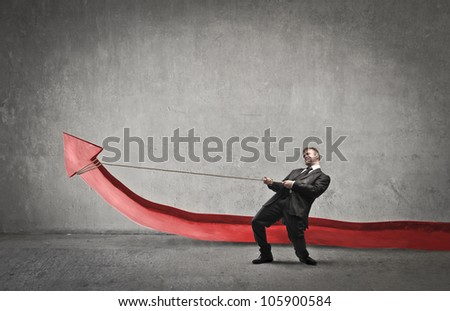 Businessman trying to lift a red arrow by pulling it with the help of a rope - stock photo