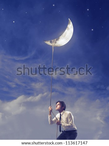 Businessman trying to pull down the moon with a rope