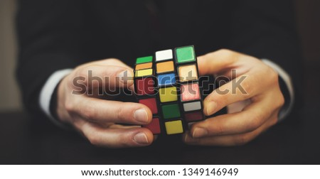 Businessman trying to solve rubik cube