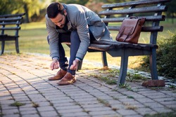 businessman tying shoes while sitting on a bench in a park