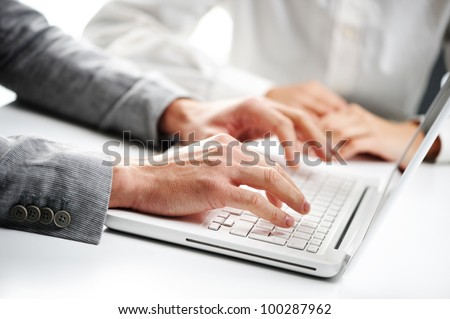 businessman typing on a white computer keyboard, woman on background