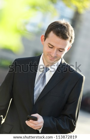 Businessman typing on the cell phone