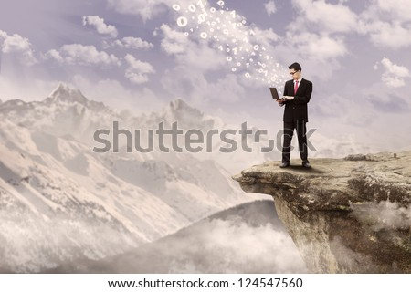 Businessman typing with his laptop on top of a mountain