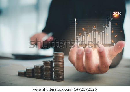 businessman use calculator plans to increase business growth and an increase in the indicators of positive growth in 2020 on virtual screen.stacking money coins.