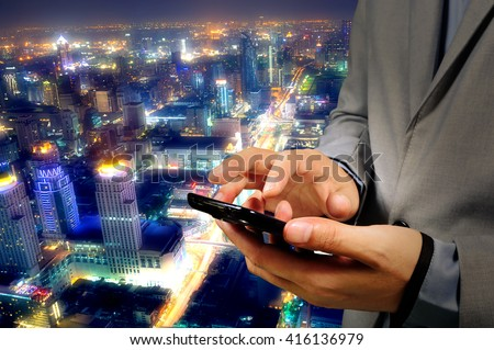 Businessman use Mobilephone or Smartphone with Modern City Background #416136979
