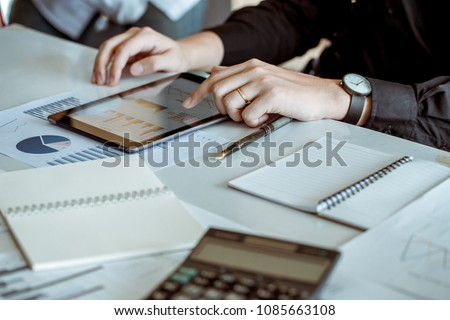 Businessman use tablet computers to connect with the word for analyse economics trade. He is married. He touching screen pad.