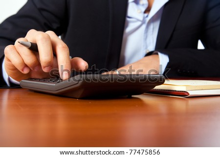 Businessman using a calculator on a wooden desk.