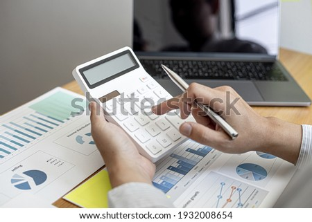 Businessman using a calculator to calculate numbers on a company's financial documents, he is analyzing historical financial data to plan how to grow the company. Financial concept.