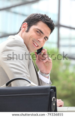 Businessman using a cellphone outside