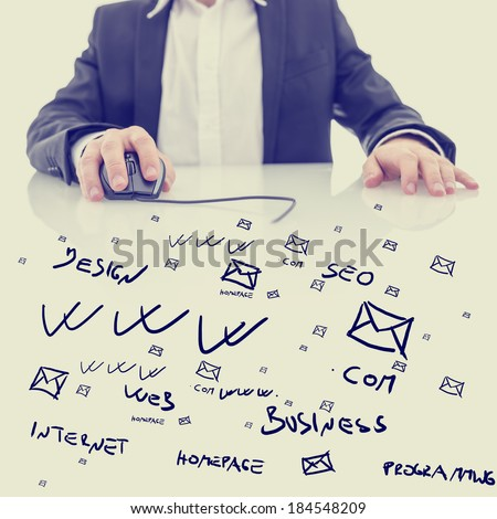 Businessman using a computer mouse sitting at a glass topped desk covered in hand-drawn computing, business and e-commerce icons and notations in a conceptual image. With retro filter effect.