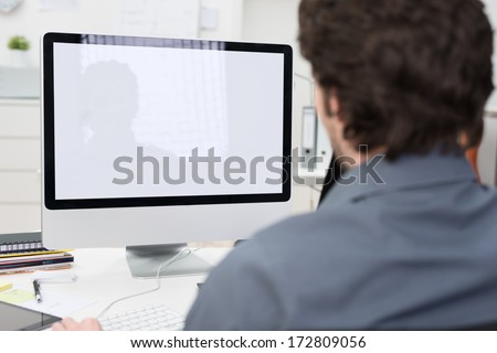 Businessman using a desktop computer with a view over his shoulder from behind of the blank screen of the monitor #172809056