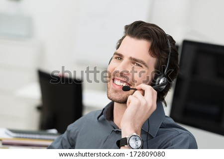 Businessman using a headset for hands free communication or a young call centre operator taking a call at the help desk