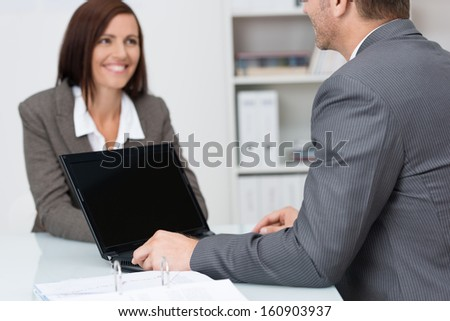 Businessman using a laptop computer in a meeting with a female colleague with focus to the blank screen of the computer