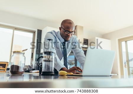 Businessman using a laptop on kitchen table at home. Man working while having breakfast. #743888308