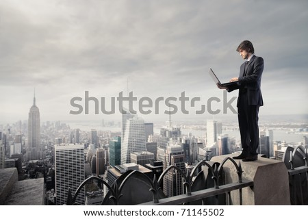 Businessman using a laptop on the rooftop of a skyscraper #71145502