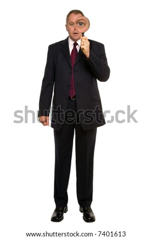 Businessman using a magnifying glass for a close inspection.