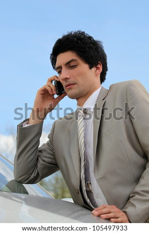 Businessman using a phone by his car