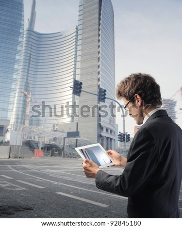 Businessman using a tablet pc on a city street