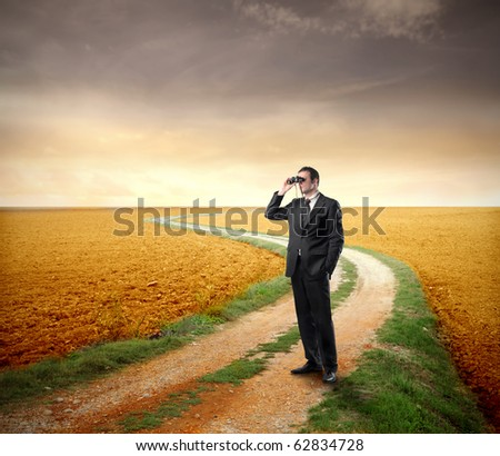 Businessman using binoculars in the country