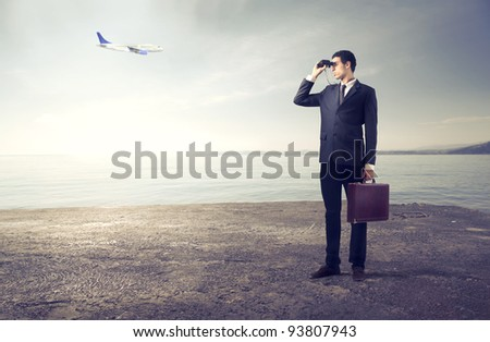 Businessman using binoculars with airplane in the background